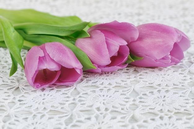Verse paarse tulpen op een mooi gehaakt tafelkleed