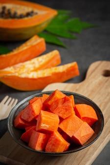 Verse papaja, in stukjes gesneden, op een zwarte plaat gelegd.