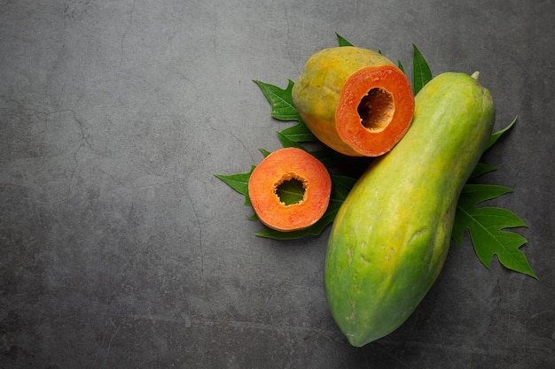 Verse papaja, in tweeën gesneden, op een donkere vloer gelegd