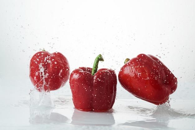 Verse paprika's vallen in helder water. verse rode peper in een scheutje water op een witte achtergrond.