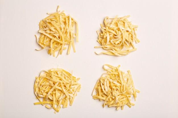 Verse pasta achtergrond zelfgemaakte italiaanse fettuccine pasta gekookt in de huis keuken met verse eieren en bloem op een witte lichte achtergrond italiaans eten en keuken concept hoge kwaliteit foto