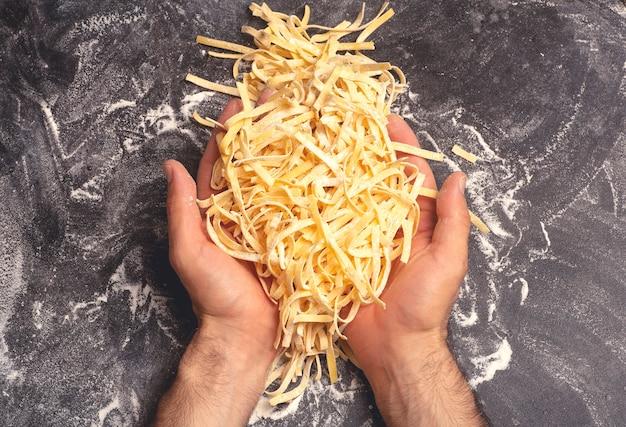 Verse pasta achtergrond zelfgemaakte italiaanse fettuccine pasta gekookt in de huiskeuken met verse eieren en bloem op een houten achtergrond italiaans eten en keuken concept hoge kwaliteit foto