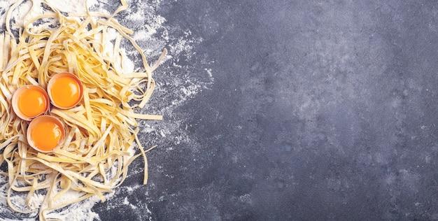 Verse pasta banner achtergrond zelfgemaakte italiaanse fettuccine pasta gekookt in de huis keuken met verse eieren en bloem op een houten achtergrond italiaans eten en keuken concept hoge kwaliteit foto