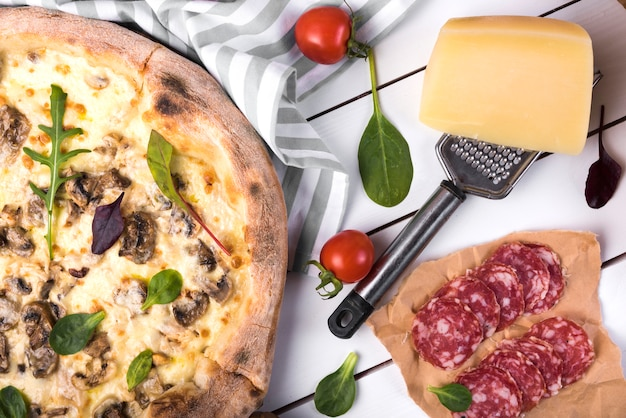 Verse pepperoni met groenten; kaas; rasp en heerlijke pizza's over houten paneel