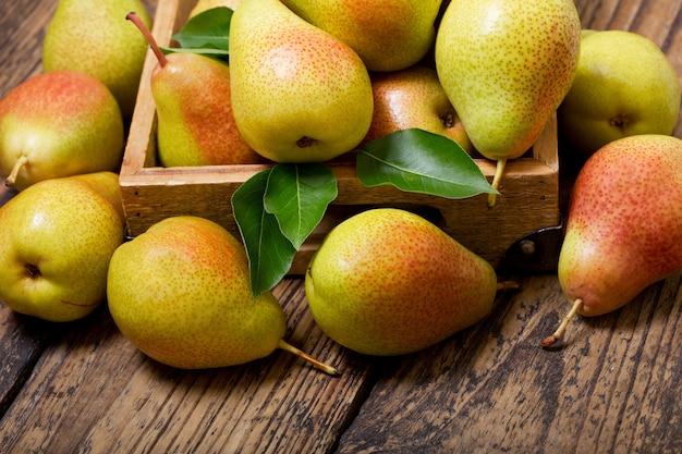 Verse peren met bladeren in een doos op houten tafel