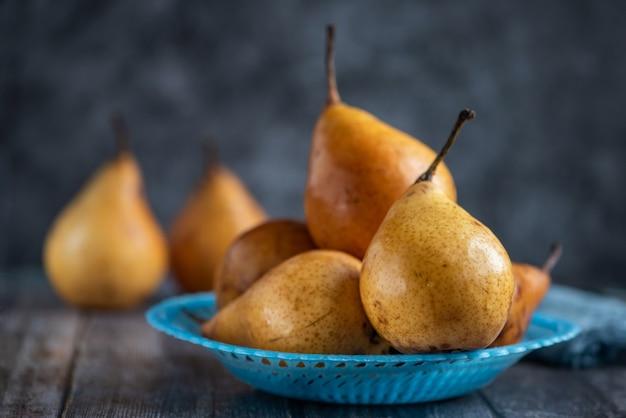 Verse peren op donker hout. zijaanzicht.