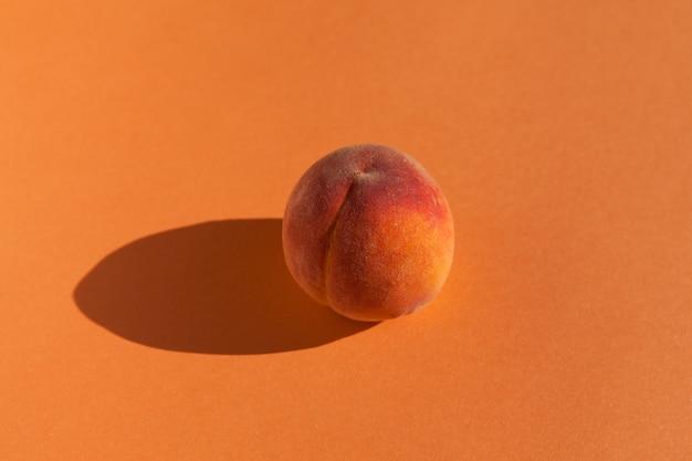 Verse perzik op een oranje achtergrond.