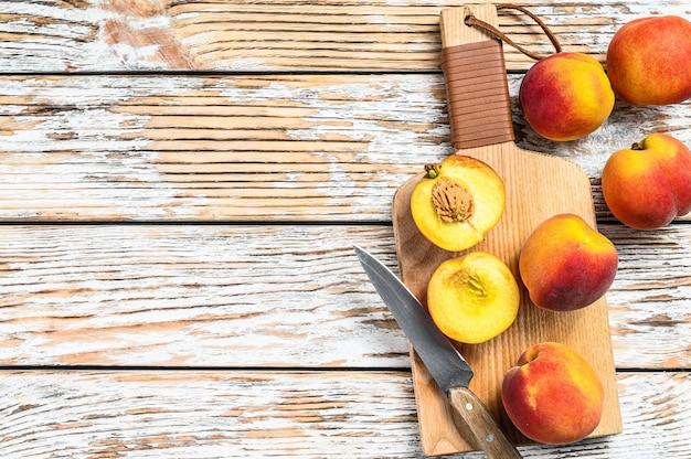 Verse perziken, biologisch fruit op de snijplank.