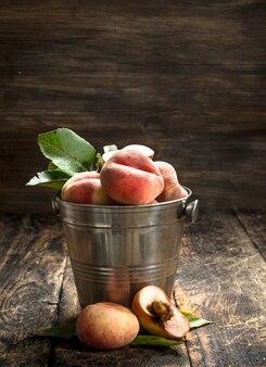 Verse perziken in een emmer met bladeren op een houten achtergrond