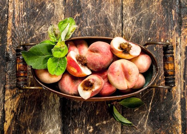 Verse perziken in een kom op een houten achtergrond
