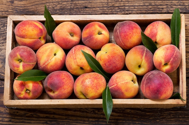 Verse perziken met bladeren in een houten kist, bovenaanzicht