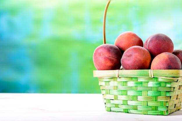 Verse perziken op een houten tafel naast de mand