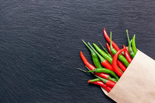 Verse pittige rode en groene paprika in een zak van kraftpapier op een leisteen bord, verschillende kleurrijke chilipepers en cayennepeper op donkere achtergrond van bovenaf. bovenaanzicht, kopieer ruimte.
