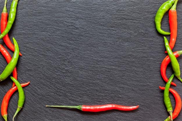 Verse pittige rode en groene peper op een leisteen bord, verschillende kleurrijke chilipepers en cayennepeper op donkere achtergrond van bovenaf. bovenaanzicht, kopieer ruimte.