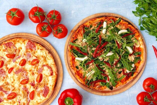 Verse pizza met kruiden en zongedroogde tomaten op grijze tafel