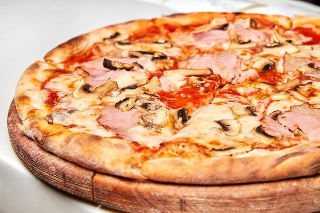 Verse pizza met spek, tomaten, champignons en kaas op een lichte achtergrond