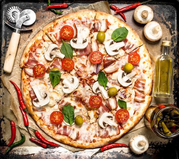 Verse pizza met spek, tomaten, olijven en greens. op het zwarte bord.