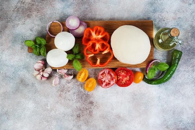 Verse pizzaproducten liggen op een concrete achtergrond. horizontale foto met kopie ruimte. bovenaanzicht