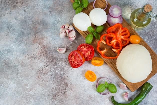 Verse pizzaproducten liggen op een concrete achtergrond. horizontale foto.
