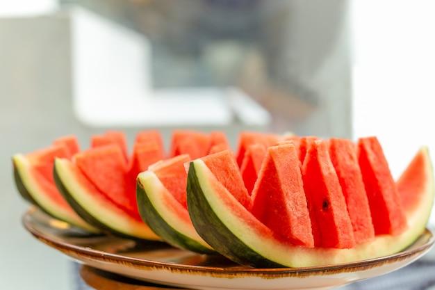 Verse plak van watermeloen op dienblad op onduidelijk beeldachtergrond.