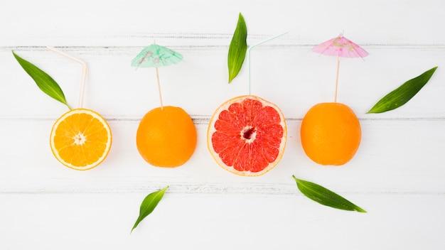 Verse plakjes citrusvruchten met decoratieve parasols en groene bladeren