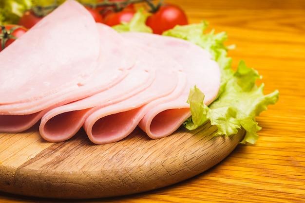 Verse plakjes ham met lattuce en cherrytomaat op de houten plank