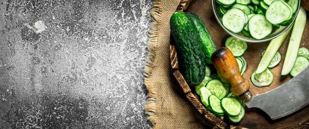 Verse plakjes komkommers op een houten dienblad. op een rustieke achtergrond