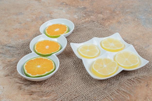 Verse plakjes sinaasappel en citroen op verschillende borden.