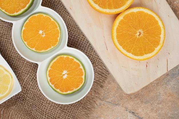Verse plakjes sinaasappel op verschillende borden.