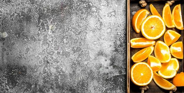 Verse plakjes sinaasappelen in een houten bakje op een rustieke achtergrond