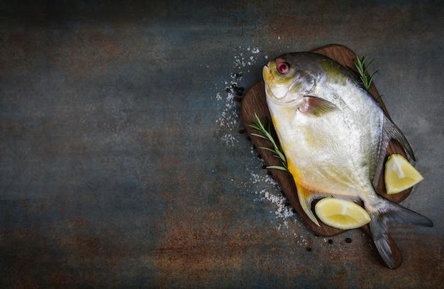 Verse pomfretvissen met de rozemarijn van kruidenkruiden en citroen op houten scherpe raad en zwarte plaatachtergrond - ruwe zwarte pomfretvissen