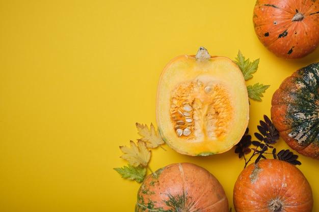 Verse pompoen op gele achtergrond, pompoen in tweeën gesneden en enkele ongebruikelijke pompoenen op gele herfstbladeren