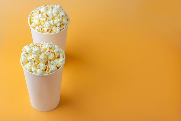 Verse popcorn in witte doos op een oranje achtergrond. cinema snack concept. het eten voor het kijken naar een film en entertainment, bovenaanzicht, plat liggen.