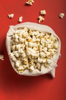 Verse popcorn morste uit de zak op een rode tafel