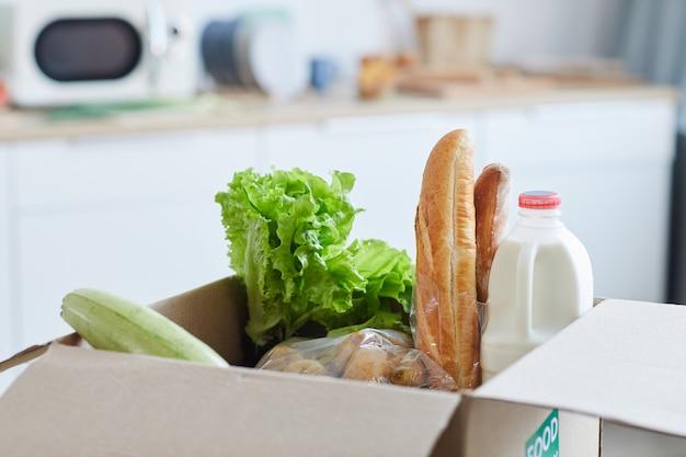 Verse producten en voedsel in kartonnen doos op tafel in keuken interieur, voedsel levering concept