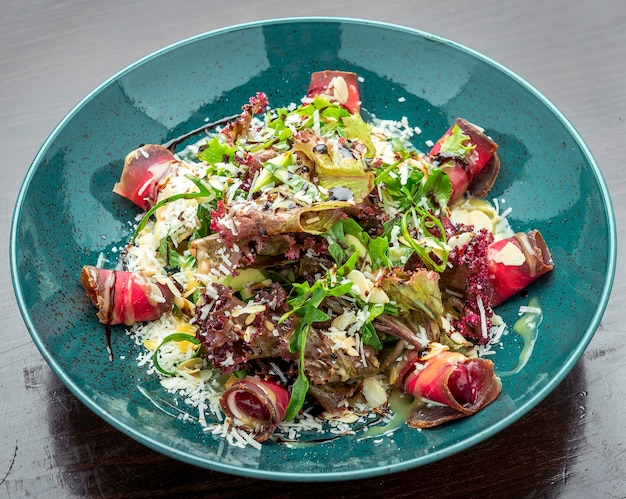 Verse prosciutto-ham en groenten salade close-up bovenaanzicht, gezonde lente salade
