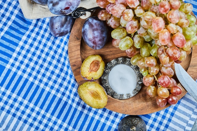 Verse pruimen en een tros druiven op houten plaat.