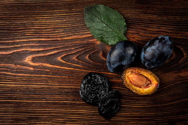 Verse pruimen en snoeien op donkere houten achtergrond.