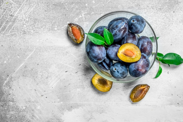 Verse pruimen in een glazen kom. op witte rustieke tafel