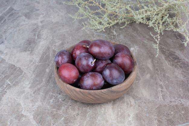 Verse pruimen in houten kom op stenen achtergrond.