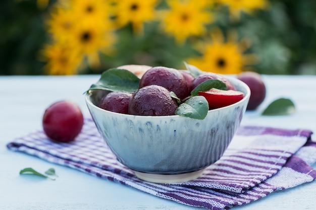 Verse pruimen met bladeren in een kom op witte rustieke houten tafel achtergrond. herfst oogst concept