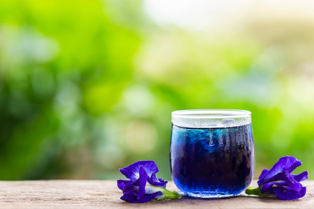 Verse purpere vlindererwt of blauwe erwtenbloem en sap in glas op houten lijstachtergrond