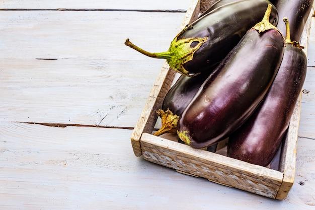 Verse rauwe aubergines in houten doos