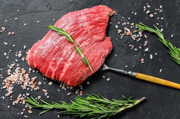 Verse rauwe biefstuk met kruiden op tafel