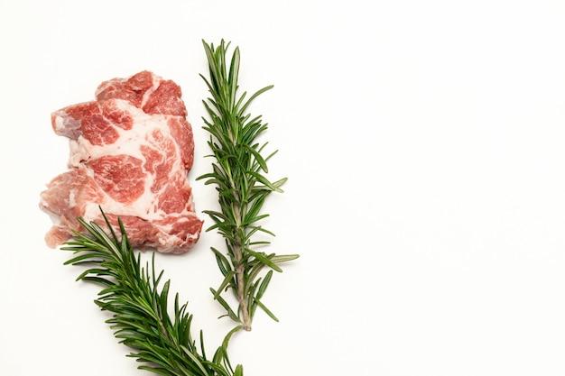 Verse rauwe biefstuk met rozemarijn geïsoleerd op een witte achtergrond, kopieer ruimte, eten thuis koken, bovenaanzicht.