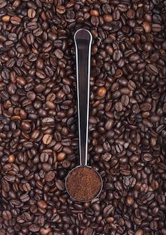 Verse rauwe biologische koffiepoeder in zilveren stalen schep bovenop koffiebonen. bovenaanzicht