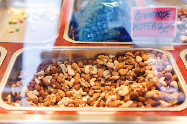 Verse rauwe biologische set, mix van noten, amandel, cashew, walnoot, hazelnoot te koop in winkelvitrine op boerenmarkt in een metalen doos. veganistisch eten, gezonde voeding, keto-voedselconcept.