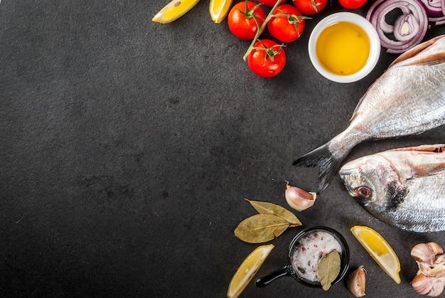 Verse rauwe biologische vis dorado zeebrasem met ingrediënten voor het koken van citroen tomaten ui zout peper laurier bladgroen olie