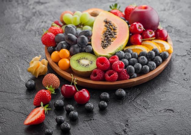 Verse rauwe biologische zomerbessen en exotisch fruit in ronde houten plaat. papaya, druiven, nectarine, sinaasappel, framboos, kiwi, aardbei, lychees, kers. bovenaanzicht