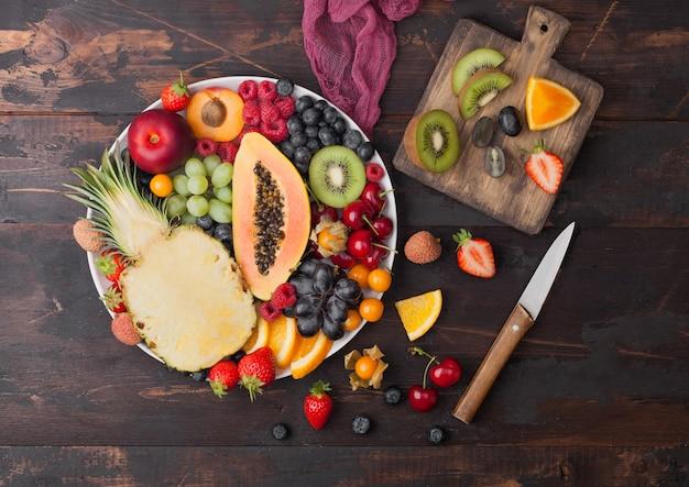 Verse rauwe biologische zomerbessen en exotisch fruit in witte plaat op donkere houten ondergrond met snijplank en mes. ananas, papaya, druiven, nectarine, sinaasappel, abrikoos, kiwi, peer. bovenaanzicht